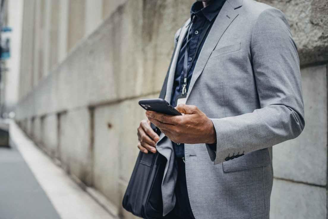 crop faceless black businessman using smartphone on sidewalk